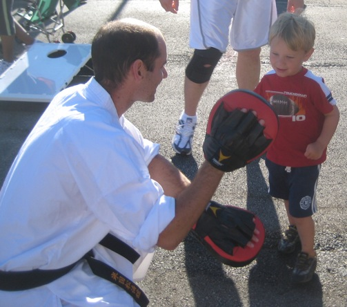 Southwest Chicago Shotokan instructor Jeff Salkas working with a future karate expert at a community event.
